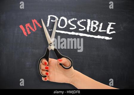 """Motivierende Nachricht auf Tafel mit Frau schneiden mit Schere das Wort """"unmöglich"""", die sich in den möglichen - Stockfoto"""