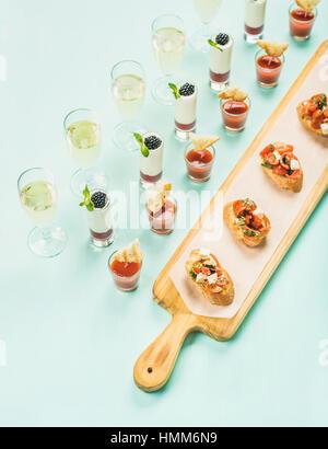 Brushettas, Gazpacho Aufnahmen, Desserts, Snacks, Champagner über Pastellblau Hintergrund - Stockfoto