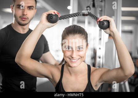 Jungen Erwachsenen persönlichen Fitness-Trainer unterstützt seine Kunden dabei Overhead Seil Erweiterung. - Stockfoto
