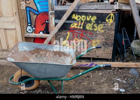 """""""Vor allem Liebe' Graffiti gesprüht über das Holzbrett; Garten Warenkorb an der Seite an die nomadische Gemeinschaft - Stockfoto"""