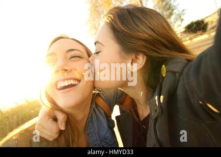 Zwei liebevolle Freunde küssen und dabei eine Selfie draußen auf der Straße bei Sonnenuntergang mit einem warmen - Stockfoto