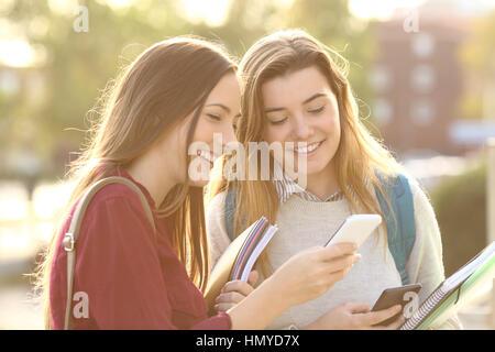 Zwei schöne Studenten beobachten Medieninhalte auf Zeile in ein smart Phone im Freien in einem Park oder einer Universität - Stockfoto