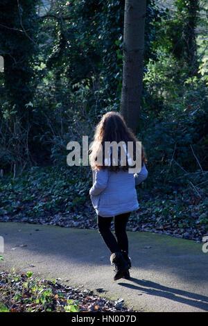 Junges Weibchen zu Fuß entfernt, durch einen Park. Sicht nach hinten. - Stockfoto