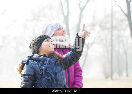 Zwei kleine Mädchen mit Mützen und Schals spielen, Tiefenschärfe und kleine Schärfentiefe - Stockfoto