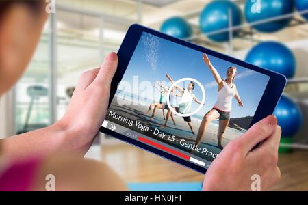 Frau mit TabletPC gegen Menschen, die Yoga am Strand - Stockfoto
