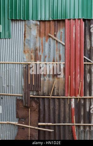 Eine Wand besteht aus der rostigen viele bunte/farbige Wellblech Blätter Reststücke. - Stockfoto