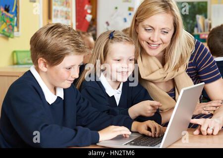 Lehrer helfen Grundschüler In Computer-Klasse - Stockfoto