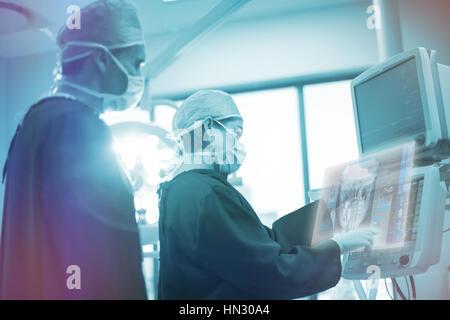 Digital erzeugte Bild menschlicher Schädel gegen Chirurgen diskutieren über Monitor in Betrieb Raum 3d - Stockfoto