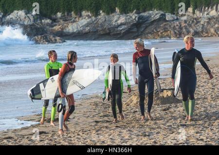 Fünf junge Surfer beenden ihre Surf-Session am Fistral in Newquay in Cornwall. - Stockfoto