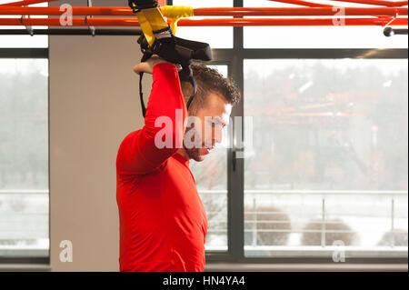 TRX Training. CrossFit Lehrer in der Turnhalle TRX-Bewegung zu tun. Fitnesstraining Mann an den Ringen. Fitness - Stockfoto