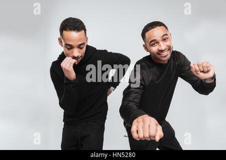Bild von zwei Jungen glücklich afrikanische Männer tanzen über weißen Hintergrund beim Blick auf Kamera und beiseite. - Stockfoto