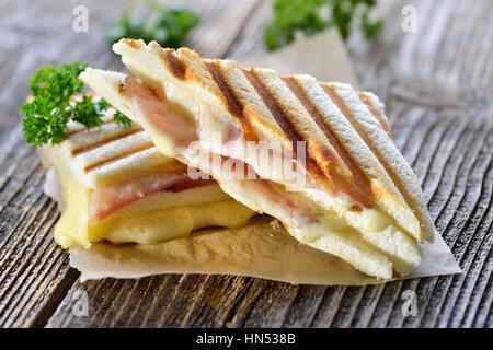 Gepresste und gerösteten doppelte Panini mit Schinken und Käse auf Butterbrotpapier auf einem Holztisch serviert - Stockfoto