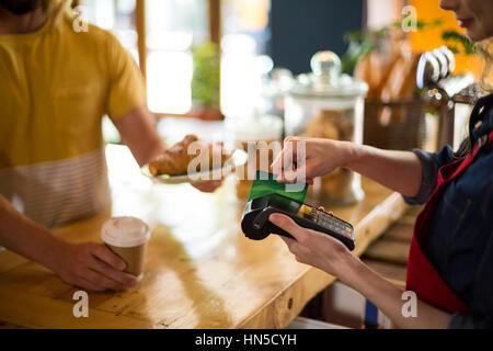 Mittelteil des Kunden die Zahlung per Kreditkarte am Schalter im Cafà© - Stockfoto