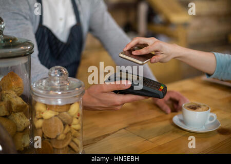 Frau, die Zahlung der Rechnung durch Smartphone mit NFC-Technologie im café
