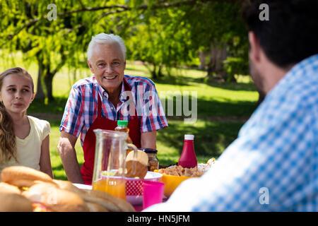 Portrait von senior Mann sitzen mit Familie an einem sonnigen Tag im park - Stockfoto