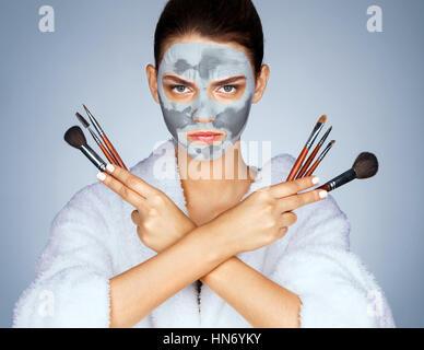 Ernst Frau Schminkpinsel hochhalten. Foto der jungen Frau mit Maske aus Ton auf ihrem Gesicht. Schönheit & Skin - Stockfoto