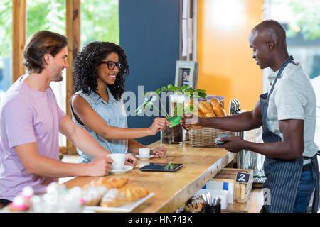 Frau, die die Zahlung durch Kreditkarte am Schalter im Cafà© - Stockfoto
