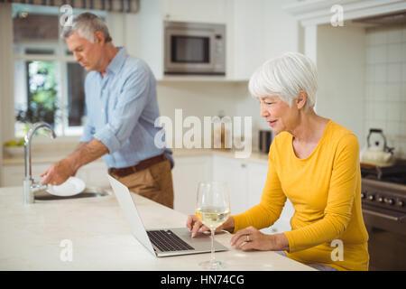 Ältere Frau mit Laptop in der Küche, während Mann Reinigung Gerichte im Hintergrund - Stockfoto