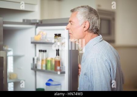 Ältere Mann auf der Suche im Kühlschrank zu Hause - Stockfoto