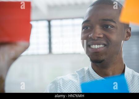 Lächelnd Geschäftsmann Lesung Haftnotizen auf Glas im Büro - Stockfoto