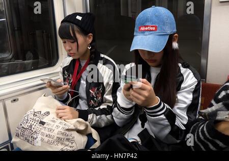 Asiaten, japanische Mädchen, junge Frauen, Freunde mit Smartphone, Reisen im Zug in Kyoto, Japan, Asien - Stockfoto