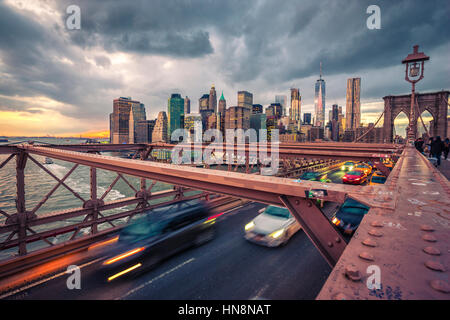 Verkehr auf Brooklyn Bridgeat bewölkten Sonnenuntergang in New York - Stockfoto