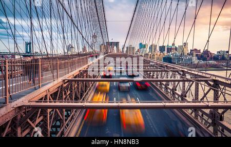 Verkehr auf Brooklyn Bridgeat bewölkten Sonnenuntergang in New York City - Stockfoto