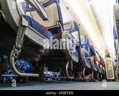 Flight Attendant dient Flugpassagiere bei einem Interkontinentalflug. Niedrigen Winkel Blick hinunter den Gang der - Stockfoto