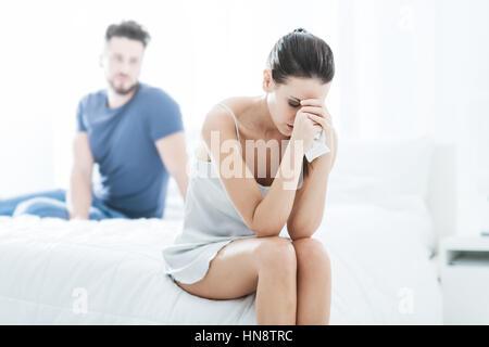 Junges Paar im Schlafzimmer, sitzt die Frau allein und zu weinen, Beziehung Schwierigkeiten Konzept - Stockfoto