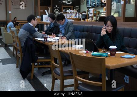 Jungen koreanischen Studenten studieren mit Handy und Tablet Ipad, asiatische Menschen arbeiten in einer Cafeteria, - Stockfoto