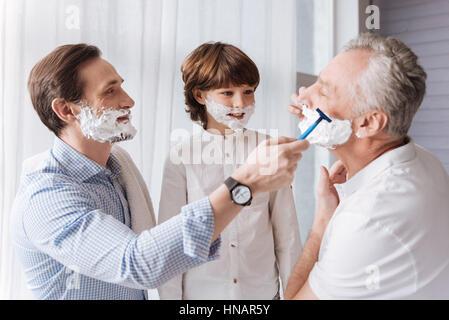 Schöne gut aussehender Mann half seinem Vater zu rasieren - Stockfoto