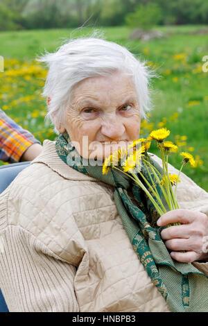 Behinderte ältere Frau sitzt in einem Rollstuhl im freien - Stockfoto