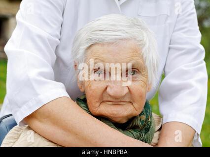 Ältere behinderte Frau in einem Rollstuhl sitzt - Stockfoto