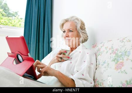 Ältere Frau mit digital-Tablette bei Kaffee am Bett zu Hause - Stockfoto