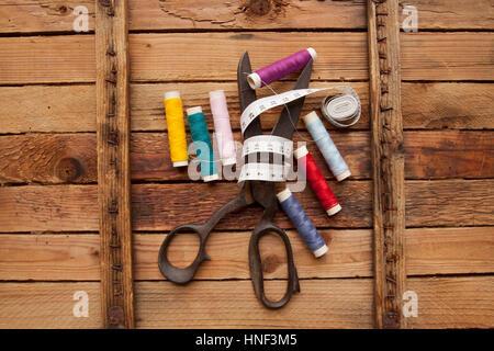 Vintage-Hintergrund mit Nähen Werkzeuge/Sewing Kit. Schere, Spulen mit Gewinde auf den alten hölzernen Hintergrund - Stockfoto