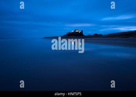 Bamburgh Castle leuchtet im Licht vor Sonnenaufgang an der Küste von Northumberland.