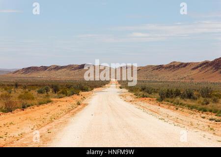 Langen weißen Kies Feldweg in Outback-Landschaft, Pilbara, Western Australia. - Stockfoto