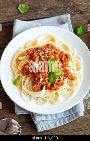 Spaghetti Bolognese Nudeln mit Tomatensauce und Hackfleisch / Faschiertes, geriebenem Parmesan und frischem Basilikum - gesunde italienische Pasta aus Eigenproduktion auf rustikal aus Holz