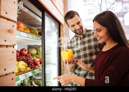 Fröhliches junges Paar Auswahl und Kauf von Gemüse im Lebensmittelgeschäft - Stockfoto