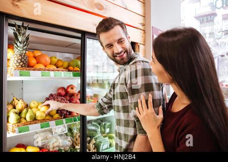 Glückliches junges Paar stehen und Auswahl Gemüse im Lebensmittelgeschäft - Stockfoto