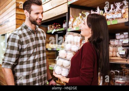 Glückliches junges Paar Marshmallows im Lebensmittelgeschäft zu kaufen - Stockfoto