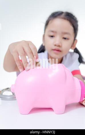 Kleine Asiatin in Thai Studenten Uniform Sparschwein selektiven Fokus auf geringe Schärfentiefe Schwein Münzen gesetzt - Stockfoto