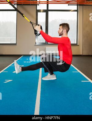 weiße lockige bärtigen sportlichen Mann mit Fitness Riemen im Fitness-Studio trainieren - Stockfoto