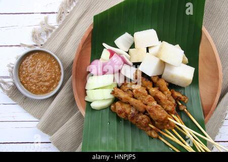 Chicken Satay. Beliebte Grillgut in Singapur und Malaysia, serviert mit Erdnuss-Sauce, Reis, Kuchen, Gurke und Schalotten.