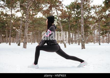 Fitness Frau Läufer dehnen Beine vor dem Training im Freien im Winterwald - Stockfoto