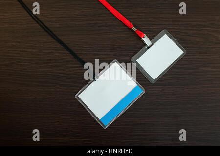 Zwei leere Identifikation Abzeichen mit schwarzen und roten Schlüsselband auf hölzernen Hintergrund - Stockfoto