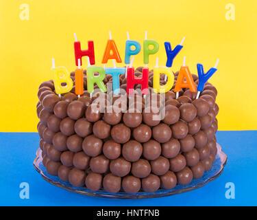 Whopper einer Schokolade Kuchen mit Süßigkeiten Malz Kugeln und Happy Birthday Kerzen dekoriert. Blaue Fläche gelben - Stockfoto