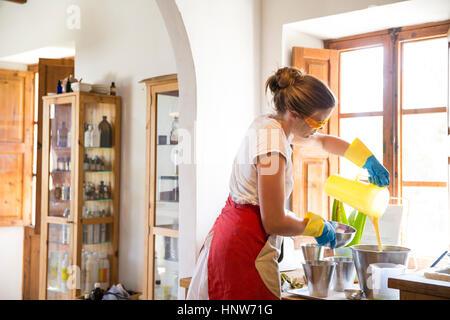 Junge Frau strömenden Flüssigkeit Lavendel Seife in Schüssel in handgemachte Seife Werkstatt - Stockfoto