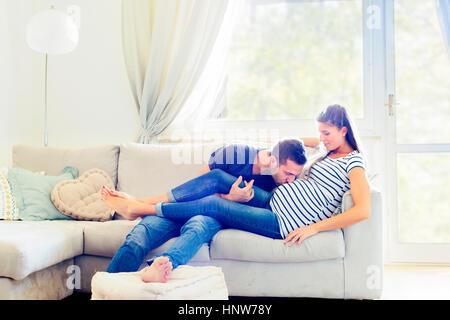 Mann auf Sofa schwangere Frau Bauch küssen - Stockfoto