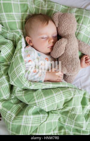 Draufsicht der Jungen schlafen auf Bett mit Teddybär - Stockfoto